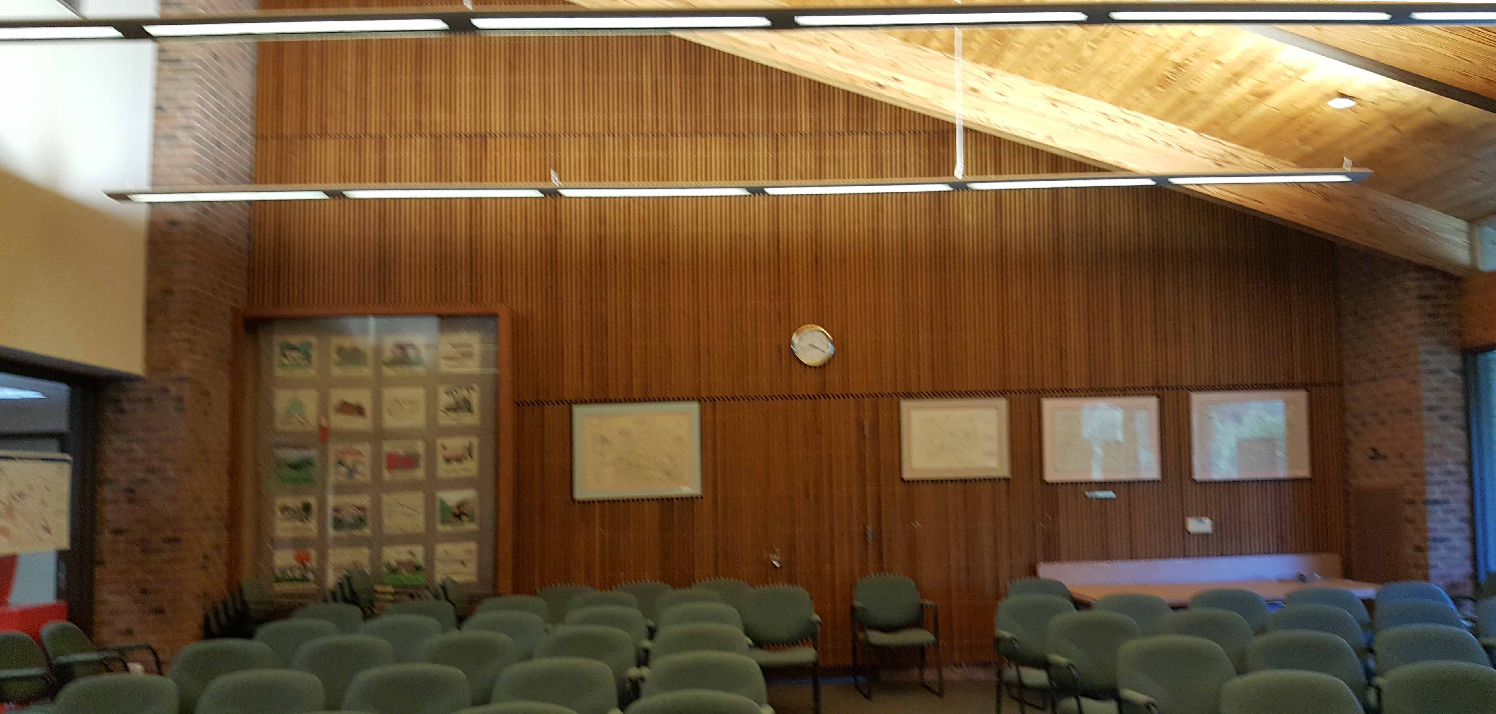 A large meeting room with wood plank ceiling faces acoustical challenges.