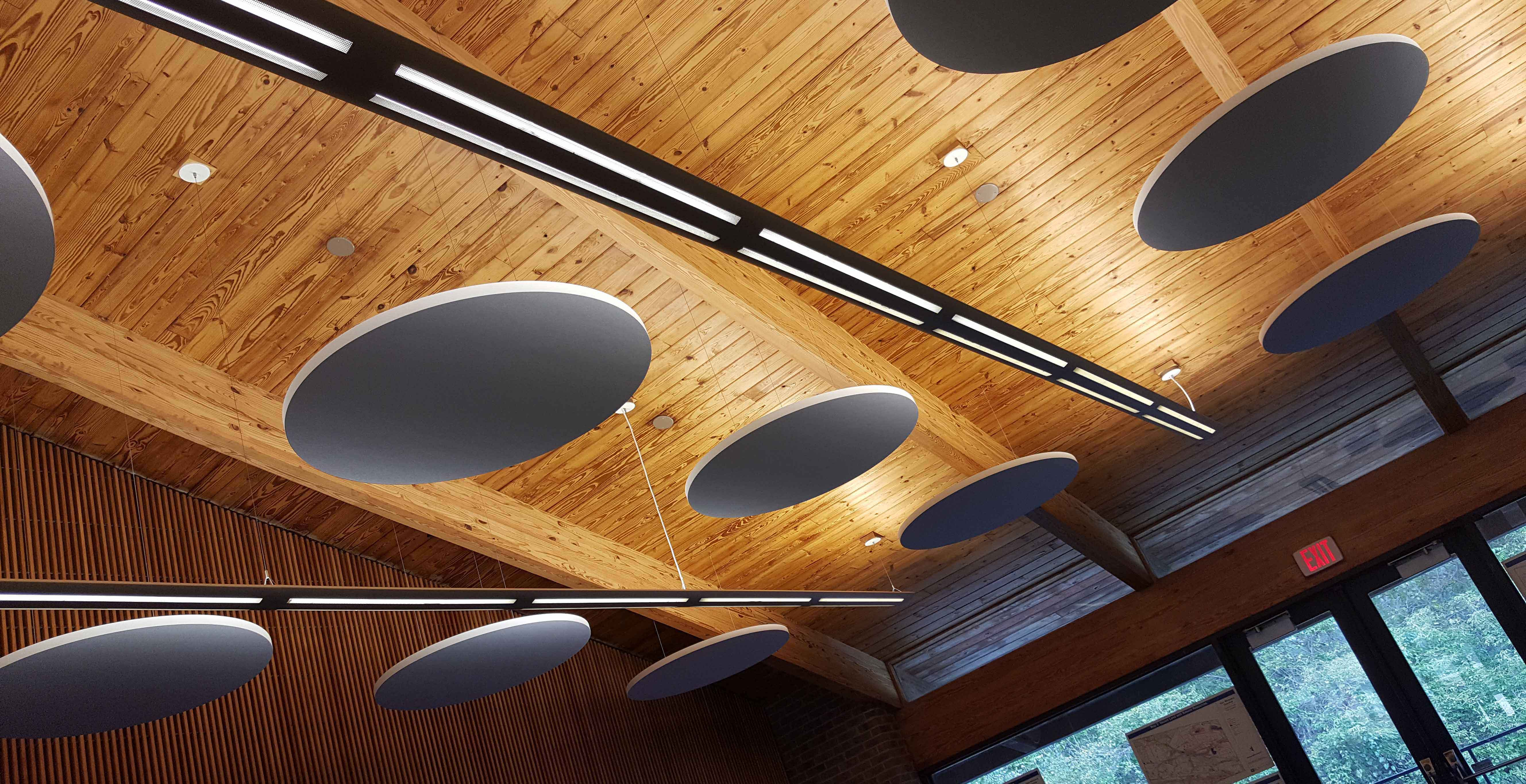 Acoustical cloud absorbers help manage sound reverberations in a large meeting room.